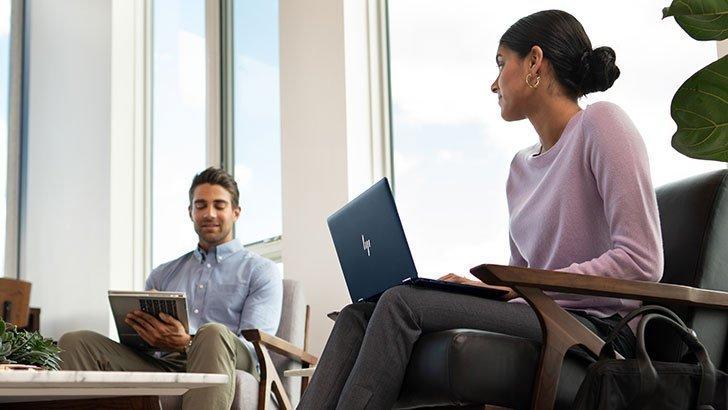 Pria dan wanita bisnis mendiskusikan pekerjaan dengan laptop HP